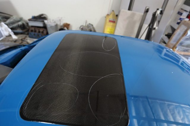 The circles are used to point out dimples in the finish on the carbon fiber sunroof-delete panel. They will be fixed before the car is race ready.