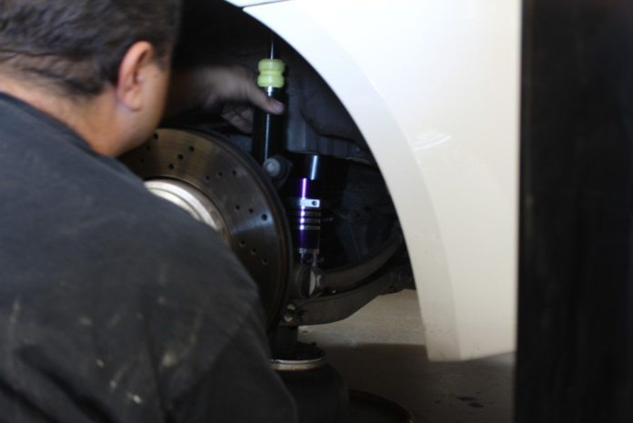 Orozco uses an air-operated jack to raise the new shocks and springs into place.