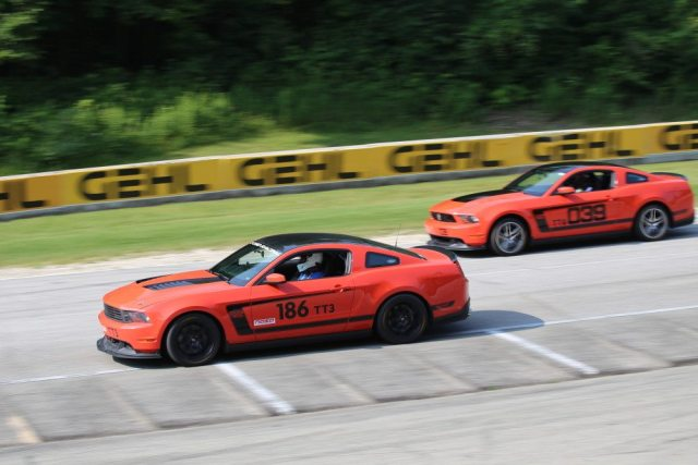 Two Boss 302 Mustangs exiting Canada Corner at full song.