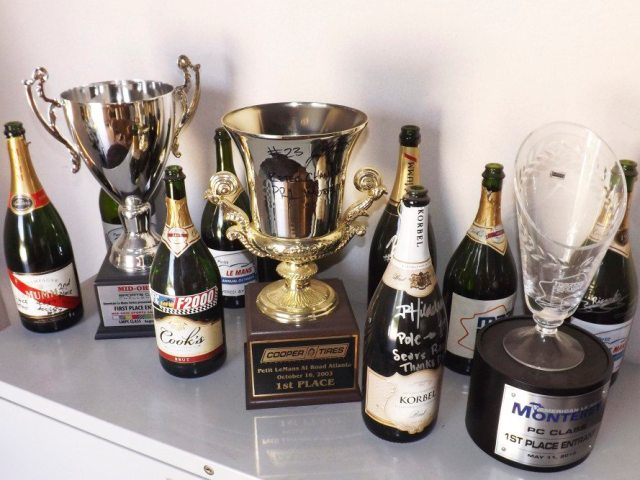 After each victory the drivers of the PR1 Motorsports Team sign the empty champagne bottles. Their shop offices have multiple shelves all over the place covered in trophies and bottles of champagne. This is just a little symbol of inspiration for team members to look at as they are prepping the cars for the next event.
