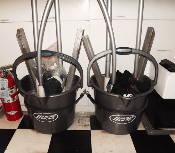 We use our ballast buckets to hold the three separate flag poles and the metal base in place. A simple eyebolt and rubber bungee hold the buckets in the trailer while traveling.