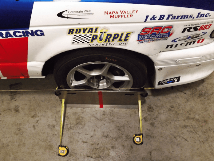 The toe plates are holding themselves up with the bungee, the plates are centered on the wheel with the red stripe, the string is showing where to make an adjustment and the two tape measures are showing what the front and rear measurements are. Now you can adjust the alignment to the toe setting you desire.
