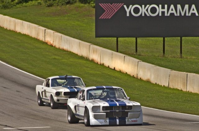 Painted in the traditional American racing colors, two V2 Mustangs enter Turn 6 at Road Atlanta.