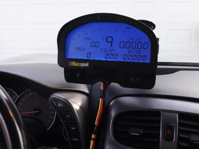 We place the display close to the driver so he or she can touch the buttons on the backing plate just below the Racepak, and so the driver can see the information on the screen, shift lights, warning lights, and lap times.