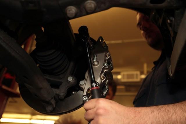Bushman torques the caliper to the mounting bracket.