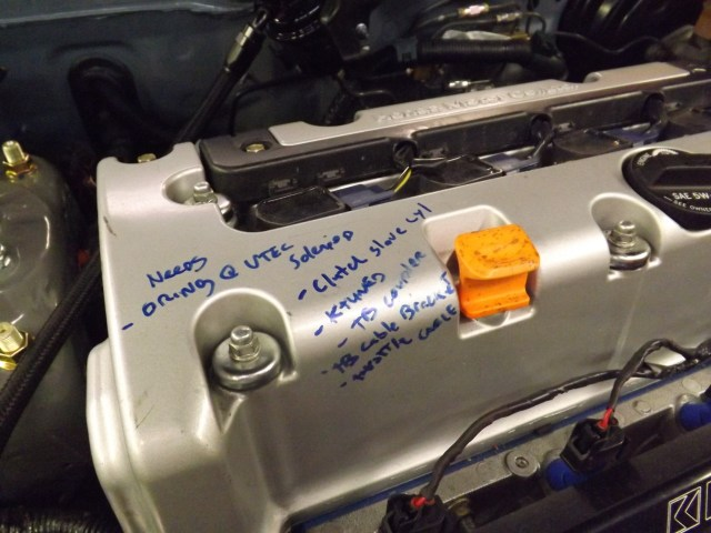 "The valve cover on Meris' Acura Integra is covered in ""to do list"" graffiti. The last item on the list is pretty important: throttle cable."