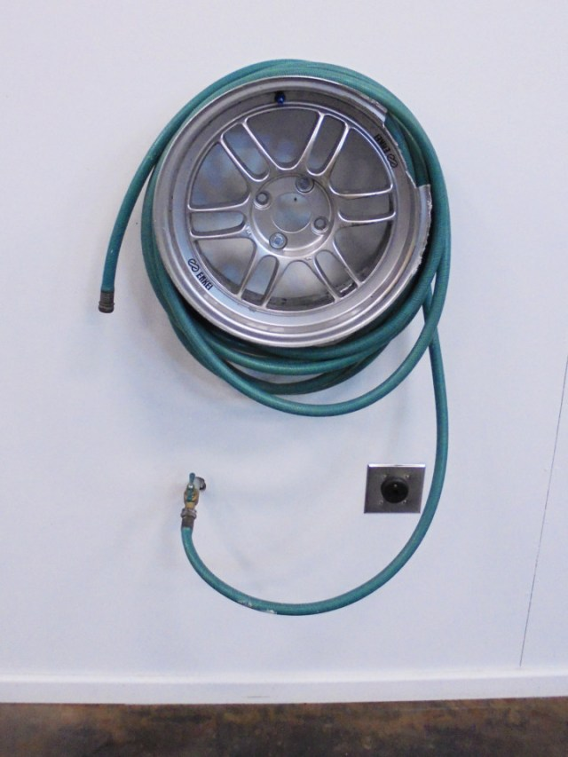 Instead of a hose reel, our shop has a hose wheel. The busted rim is a little memento from a Honda Challenge race earlier this season. Next to the hose wheel is a 130-amp receptacle for our RV.