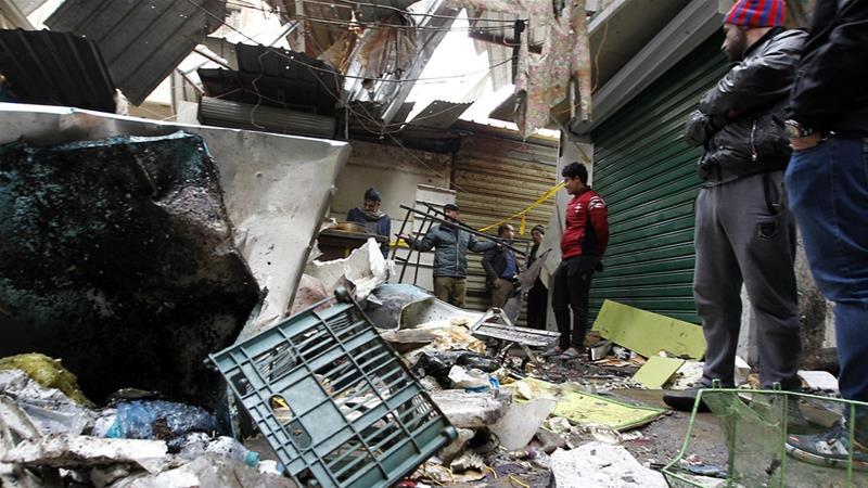 Iraqis look at the aftermath following a double blast in Al Sinak [Sabah Arar/AFP]
