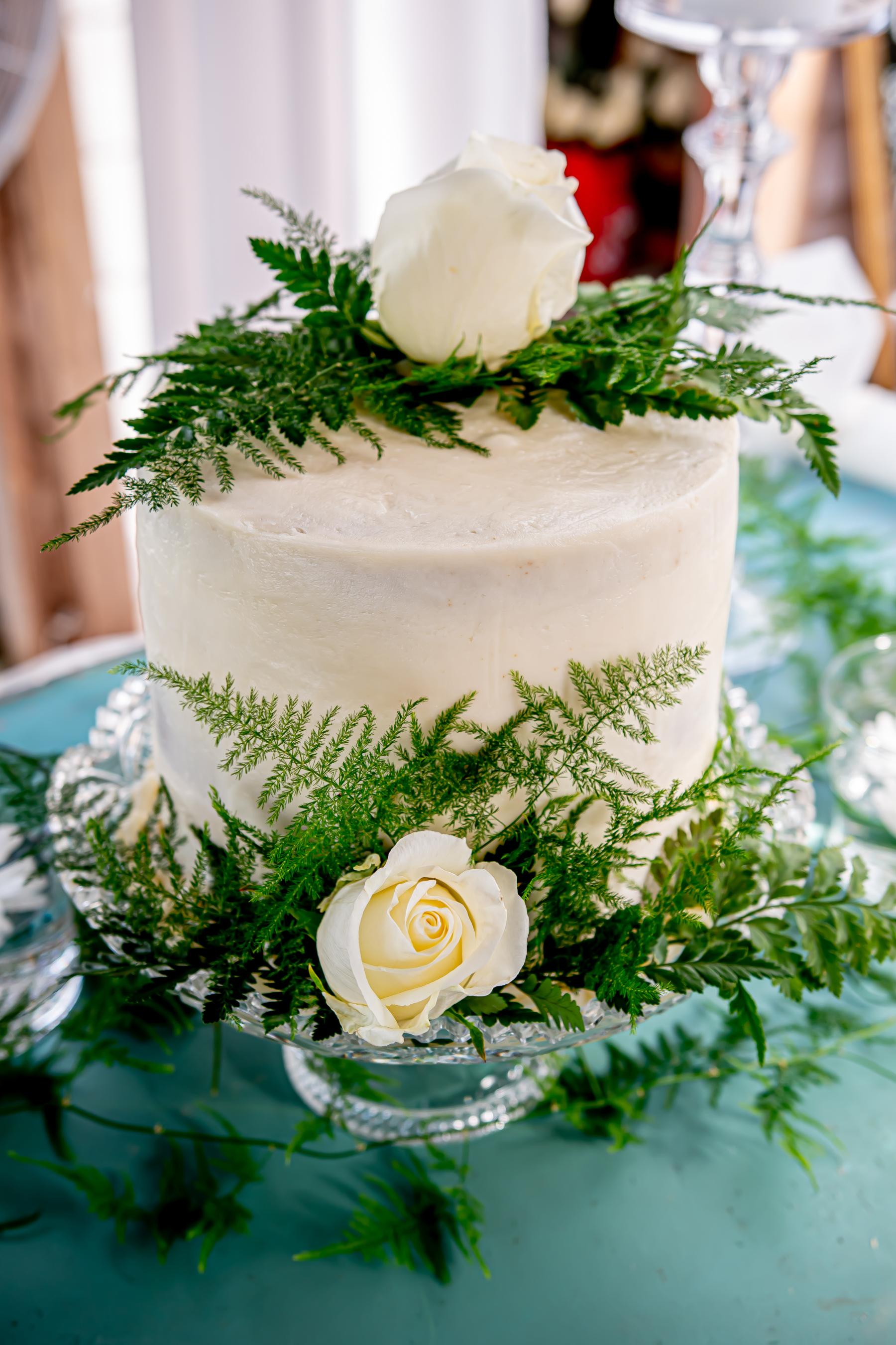 Small white wedding cake with greenery