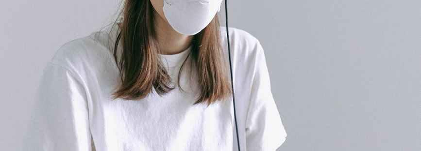 woman in white crew neck t shirt using macbook