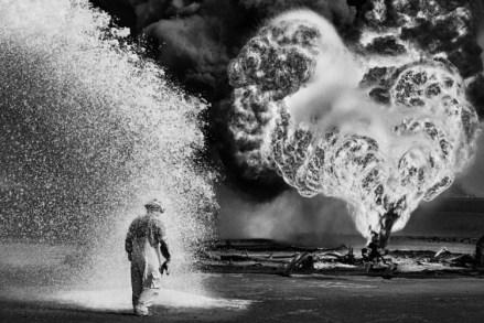 Yacimiento de petróleo del gran Burhan, Kuwait, 1991 | Durante la Guerra del Golfo, más de 500 pozos de petróleo, dinamitados por Saddam Hussein, escupían torbellinos de llamas. Este combatiente contra el fuego está protegido de la temperatura extrema por la vaporización de productos químicos.