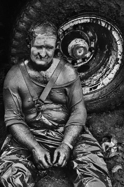 Yacimiento de petróleo del gran Burhan, Kuwait, 1991 | Técnicos especialistas del mundo entero fueron enviados para trabajar en estos pozos de petróleo en llamas. Un pequeño grupo de hombres trabaja allí de la mañana a la noche. Este ingeniero canadiense, empapado de petróleo, acaba de desmayarse y descansa apoyado en una rueda antes de reanudar el trabajo.