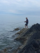Dad fishing off the rocks