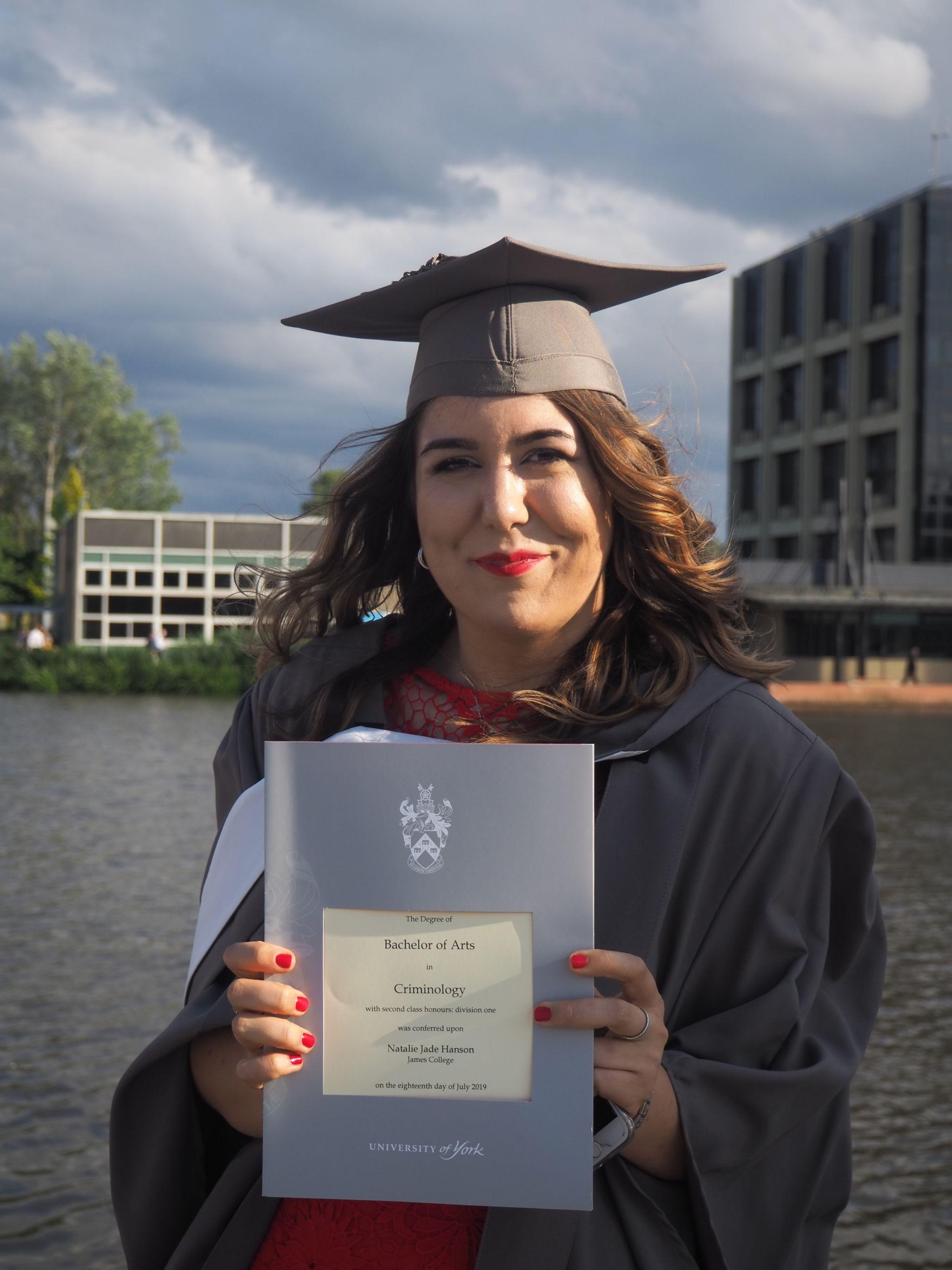 me holding my graduation certificate