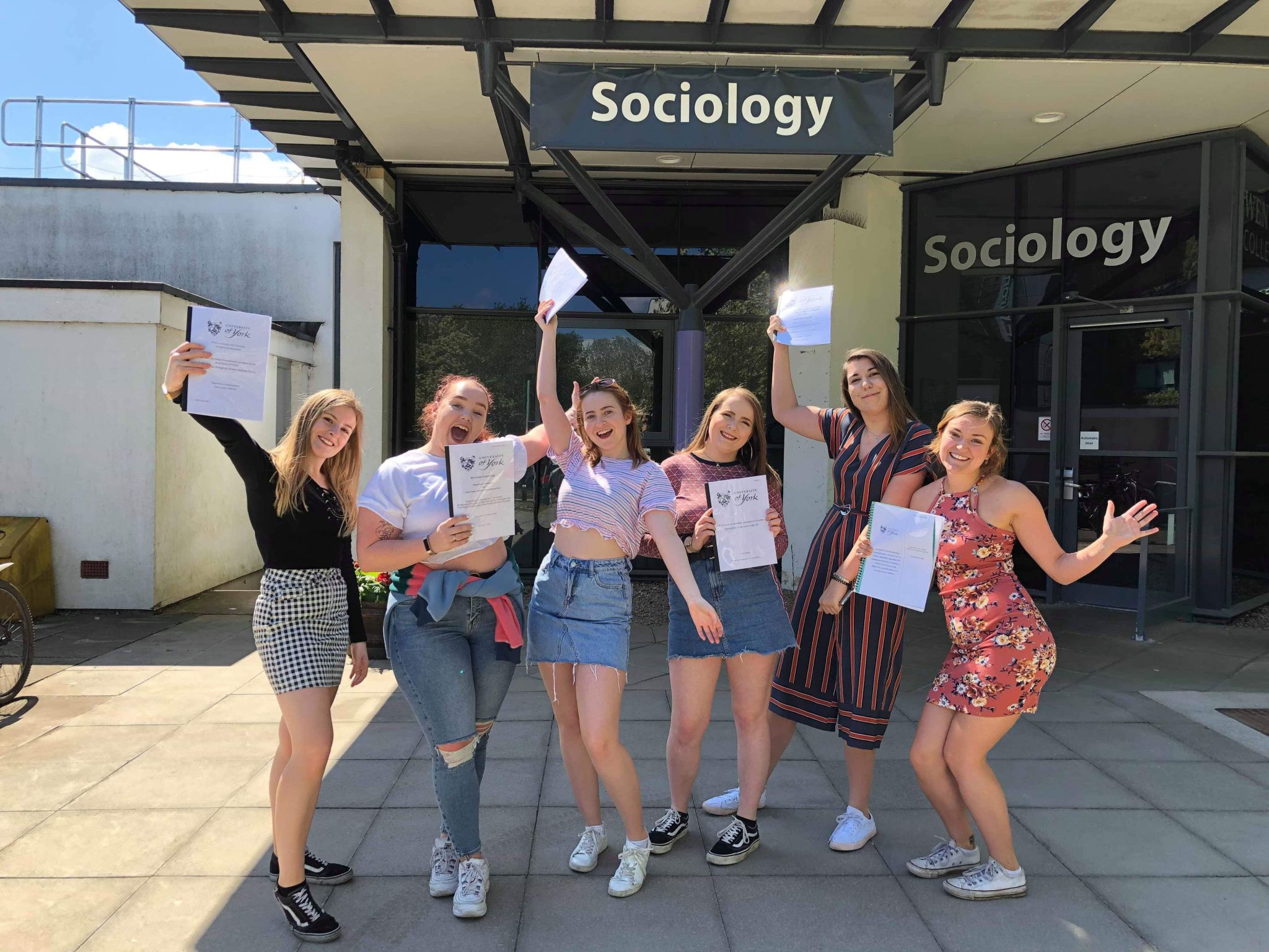 me and the girls holding our dissertations outside the department