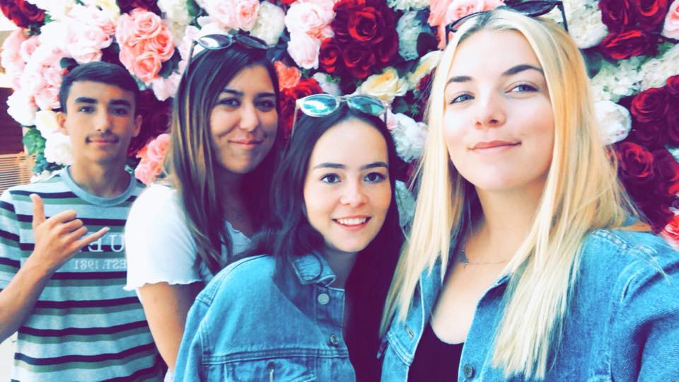 Friends and I stood in from of a pink, red, and white flower wall