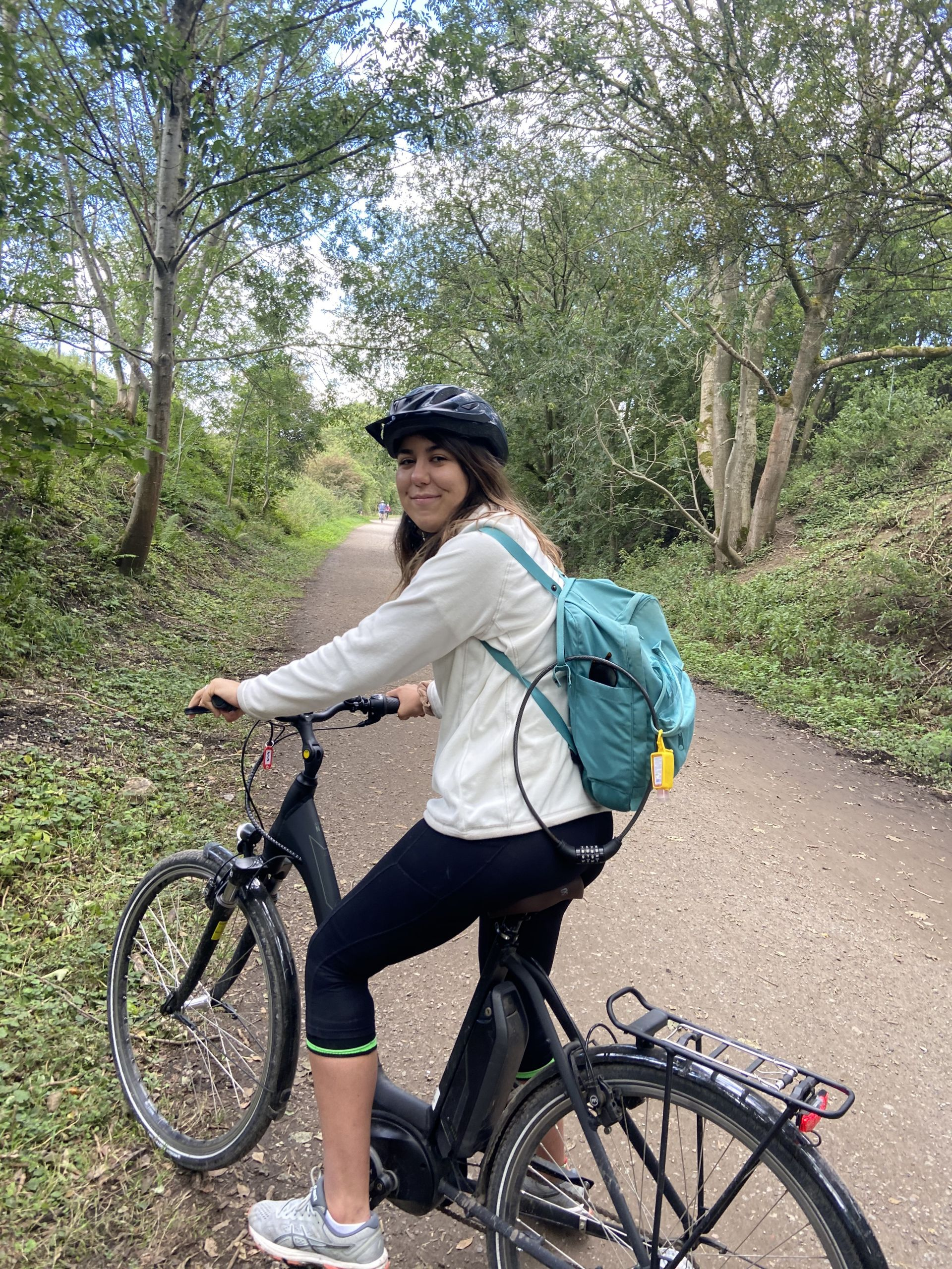 me sat on an electric bike with a white fleece and kanken on my back,