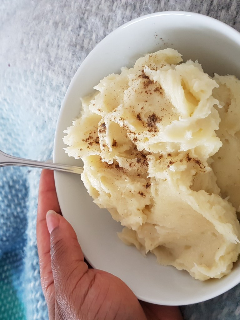 A bowl of fluffy mashed potato, seasoned with butter, salt and pepper