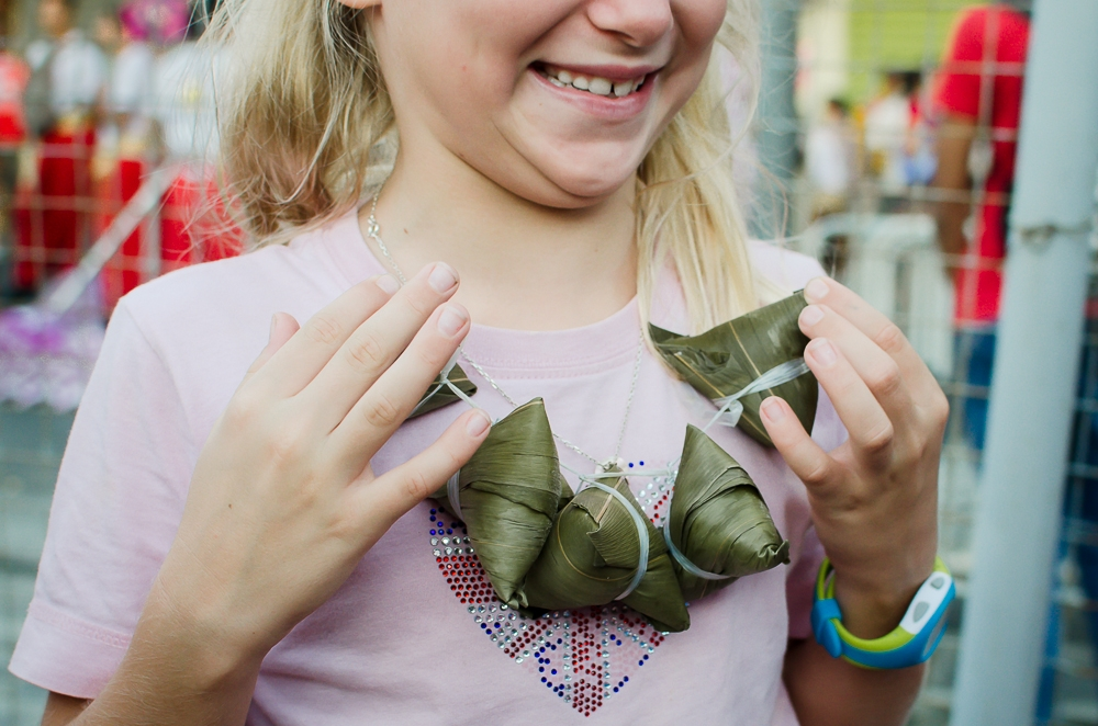 girl holds up string of sweet rice parcels in mauritius