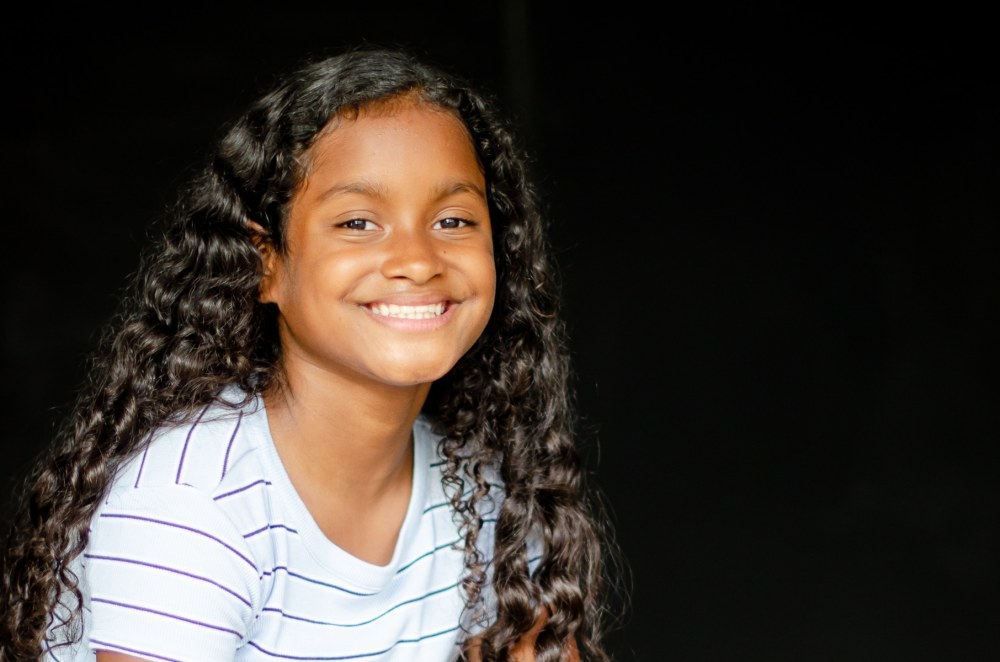 young girl smiles for the camera in a head and shoulder portrait school photo