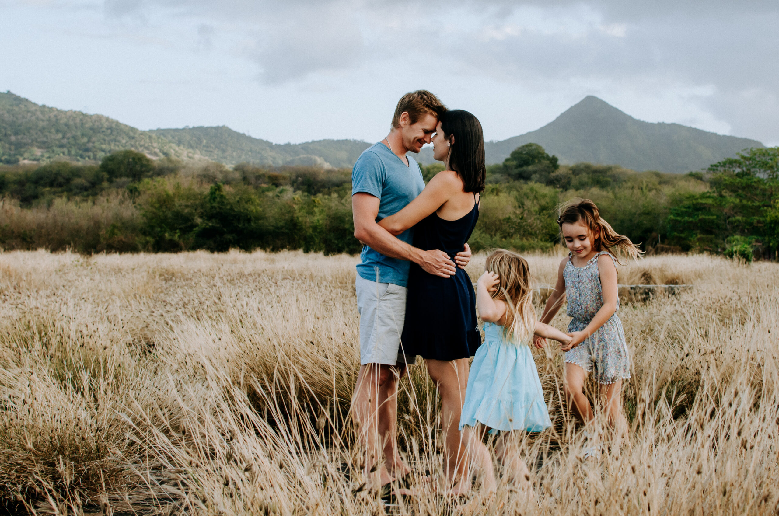 young husband and wife hug whilst their two daughters run around them in a field of long grass