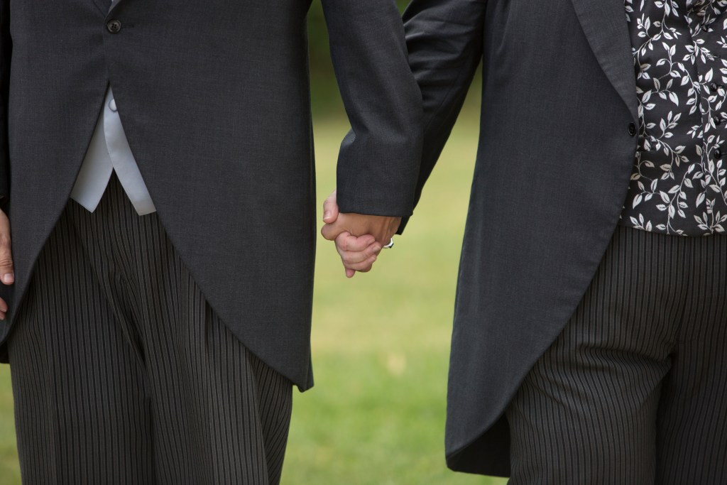 Grooms holding hands after their wedding ceremony