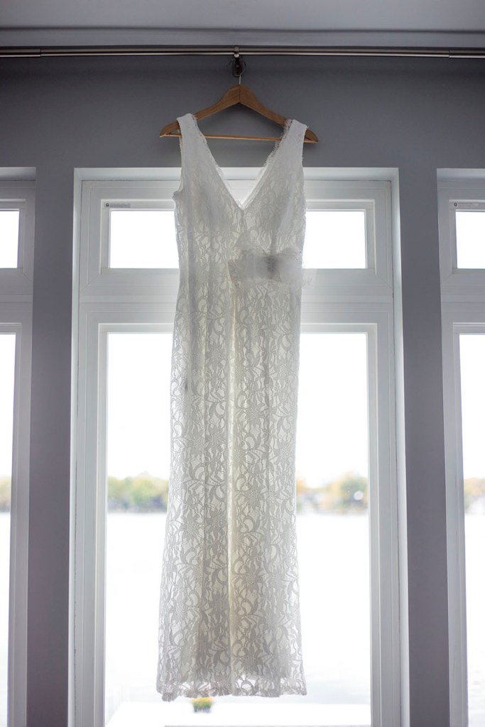 White lace dress hanging in front of a window overlooking Cavanaugh Lake in Chelsea, Michigan