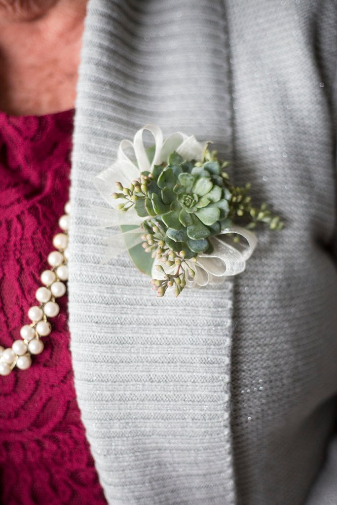 Succulent boutonnière on a gray sweater