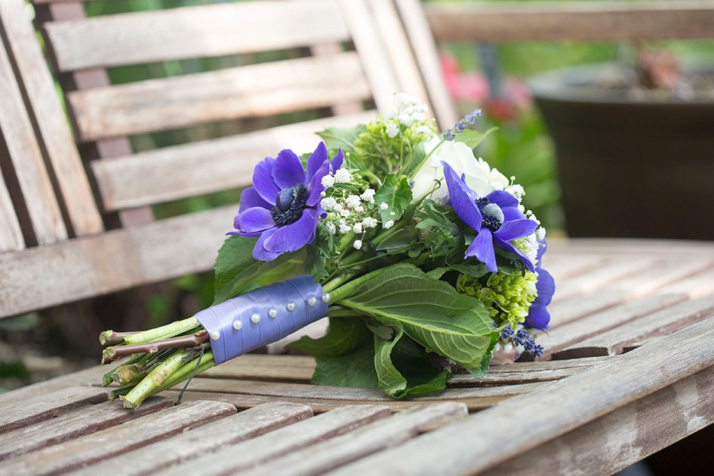 Purple and green bouquet laying on a bench inside the Belle Isle Conservatory