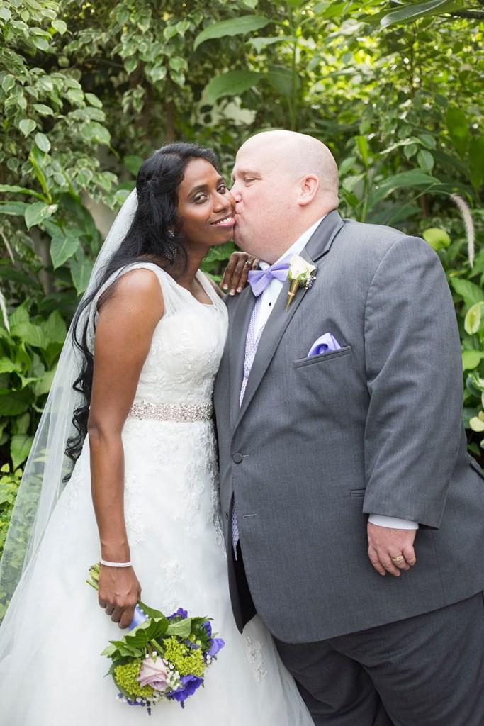 Detroit groom kisses his Michigan Indian bride