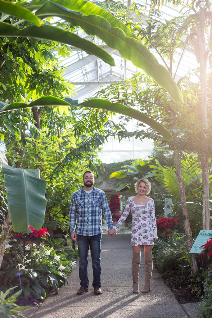 Couple-hold-hands-in-the-tropical-house