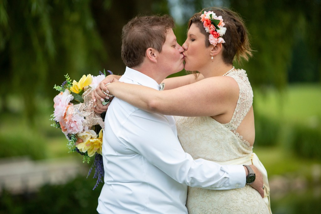 Cheryl and Emily kissing by the pond at the Links of Novi