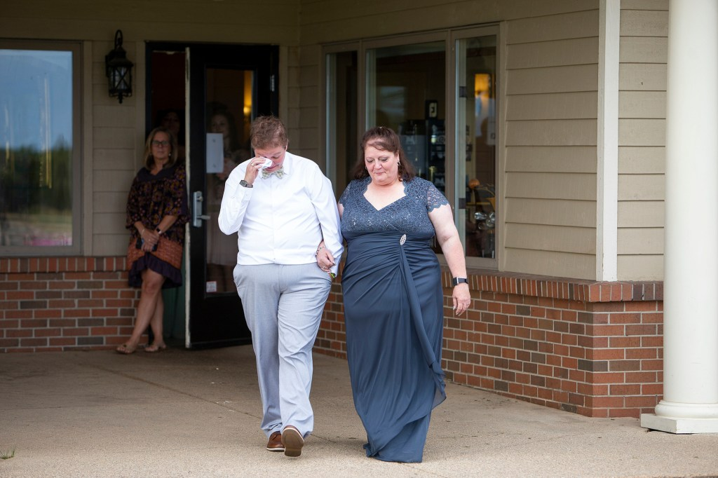 Cheryl and her mom walking down the aisle at her outdoor Michigan wedding