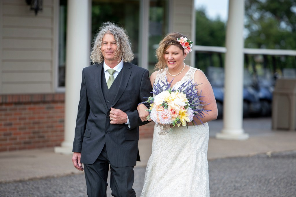 Emily and her dad walking down the aisle to meet her bride