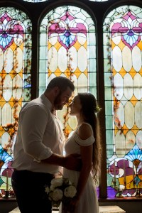 Bride and Groom in front of historic stained glass at Celebrations Wedding Chapel