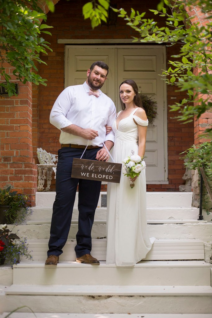 Couple poses in front of Celebrations Wedding Chapel
