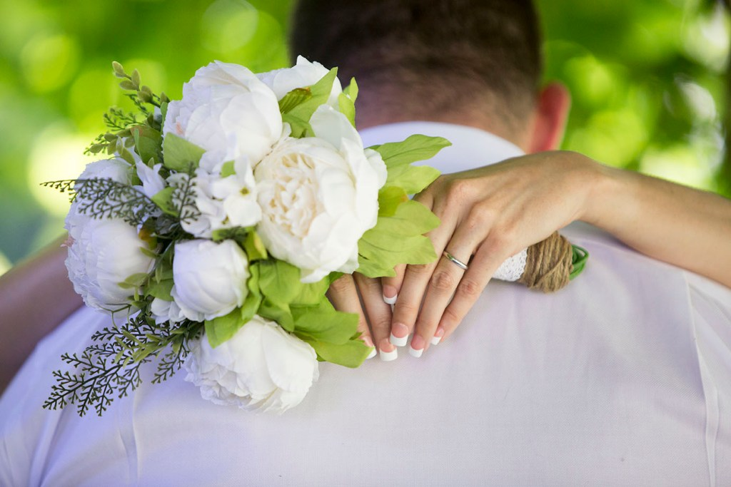 Bride wraps her arms around the groom's shoulders