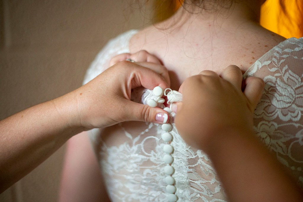 Bride's mother helps button the back of her dress