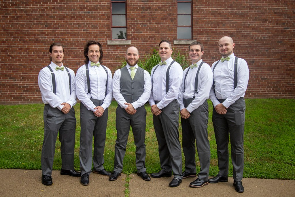 Groomsmen stand together outside the church