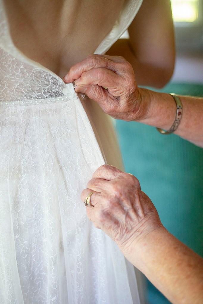 Grandma zipping bride's dress