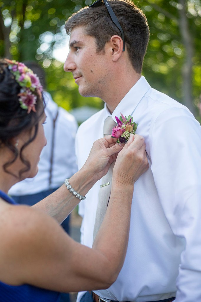 Groom getting boutonnière pinned on by mother