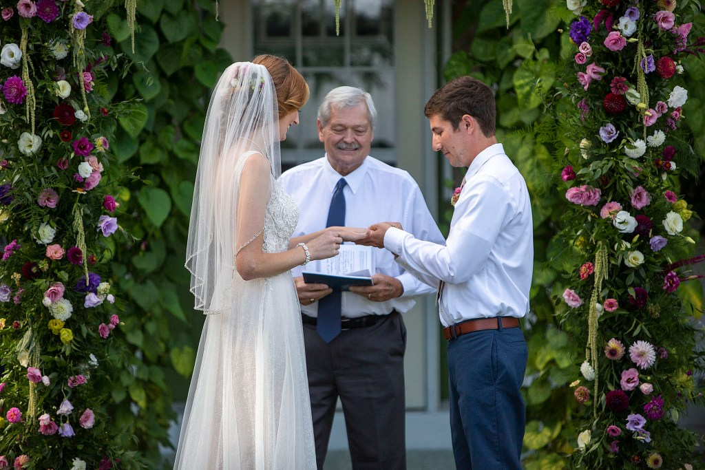 Groom puts ring on brides hand