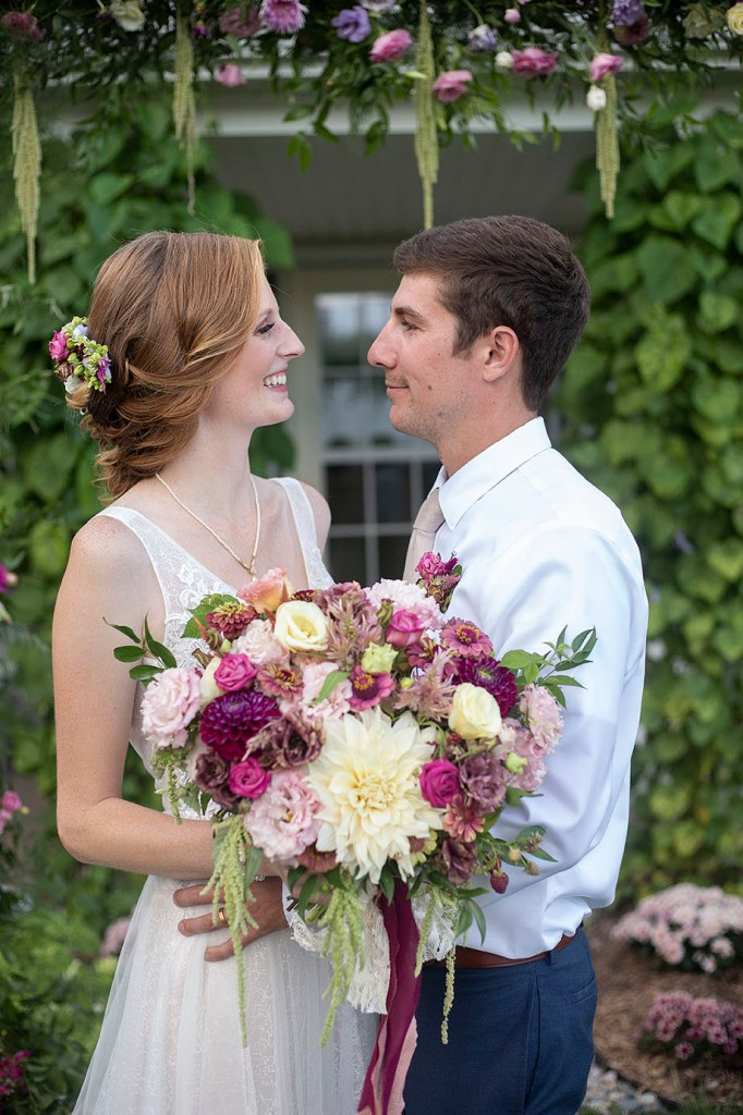 Carmen and Chris looking at each other in front of floral arbor