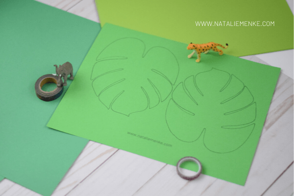 tropical leaf template on green paper with washi tape and plastic animal figurine toys