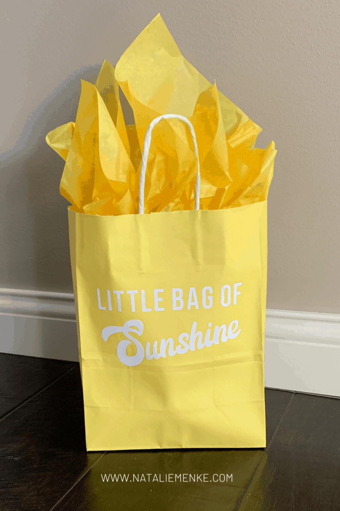 """yellow gift bag with the words """"Little Bag of Sunshine"""" and yellow tissue paper"""