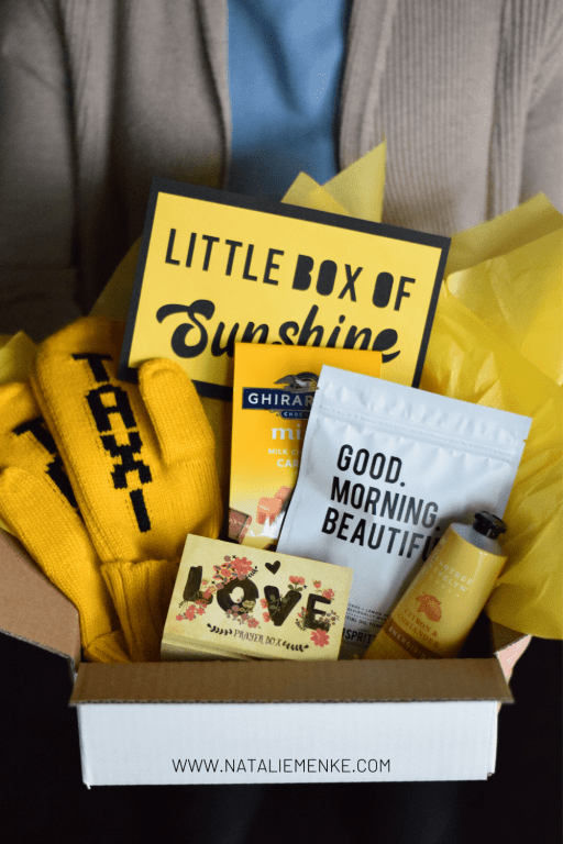 """woman's hands holding a box with yellow mittens, Ghirardelli chocolates, yellow lotion, Good Morning Beautiful towels, yellow """"love"""" box and a note saying """"Little Box of Sunshine"""""""