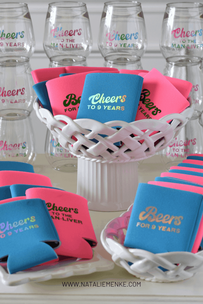 """custom pink and blue can coolers and wine glasses with the words """"Cheers to 9 years!"""""""