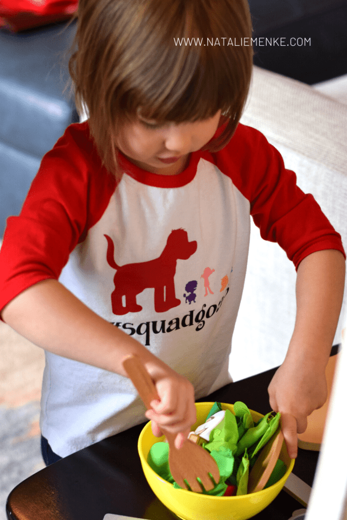 girl playing with toy food and wearing a Clifford the Big Red Dog t-shirt