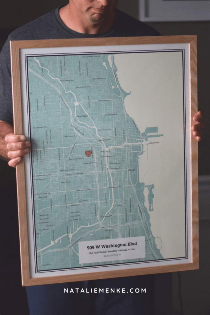 A framed The Map of Everyone held by a man