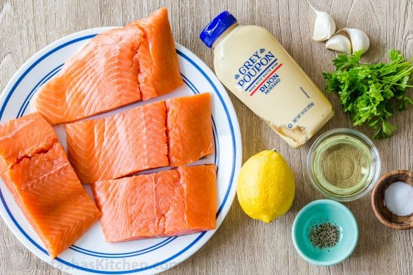 Ingredients for salmon marinade with lemon, dijon mustard, parsley, garlic, olive oil, salt and pepper
